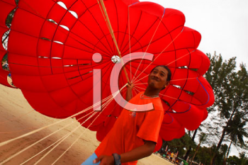 Royalty Free Photo of a Man Holding a Parachute