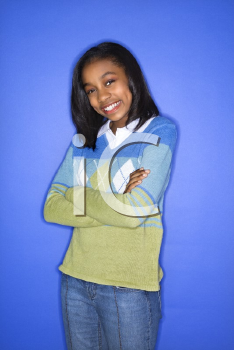 Royalty Free Photo of a Portrait of a Teen Girl With Arms Crossed Standing Smiling