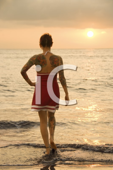 Royalty Free Photo of an Attractive Tattooed Woman on a Beach at Sunset in Maui, Hawaii, USA