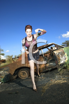 Royalty Free Photo of a Woman Hold Up a Fist in Front of an Old Rusted Car in the Junkyard