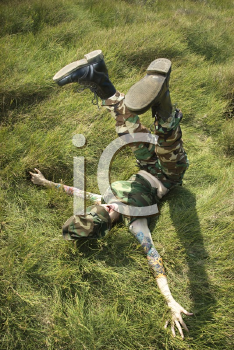 Royalty Free Photo of a Woman in Camouflage Lying on Grass With Her Legs up in the Air in Maui, Hawaii, USA