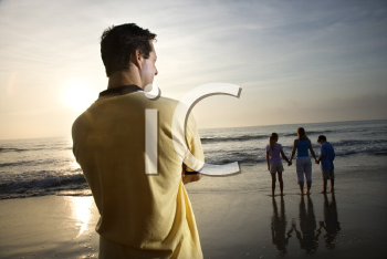 Royalty Free Photo of a Father Watching His Family on a Beach