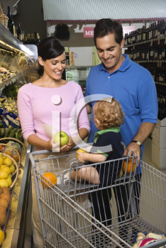 Royalty Free Photo of Parents Grocery Shopping for Fruit With Their Toddler Son