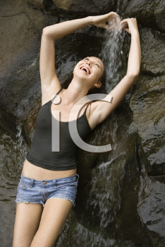 Royalty Free Photo of a Woman Standing Under a Waterfall Laughing
