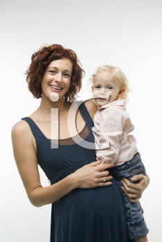 Royalty Free Photo of a Pregnant Woman Standing Holding Her Daughter