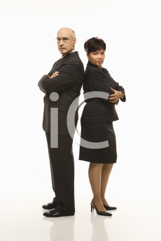 Royalty Free Photo of a Businessman and Businesswoman Standing Back to Back With Arms Crossed Looking Serious