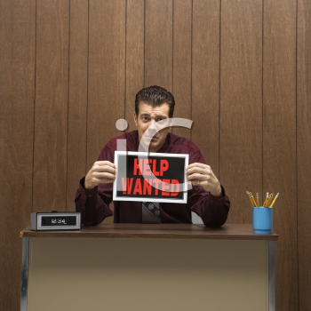 Royalty Free Photo of a Businessman Sitting at a Desk Holding a Help Wanted Sign