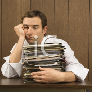 Royalty Free Photo of a Man With Overwhelmed Face Holding Lots of Paperwork