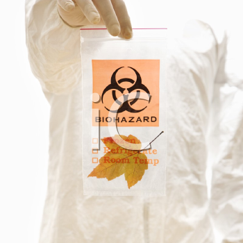 Royalty Free Photo of a Man in a Bio-hazard Suit Holding a Plastic Bio-hazard Bag Containing an Orange Maple Leaf