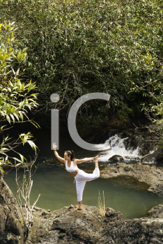 Royalty Free Photo of a Woman Doing Yoga Balancing on a Boulder by Creek in Maui, Hawaii