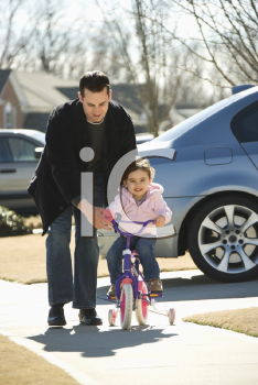 Royalty Free Photo of a Father Helping His Daughter Ride a Bicycle