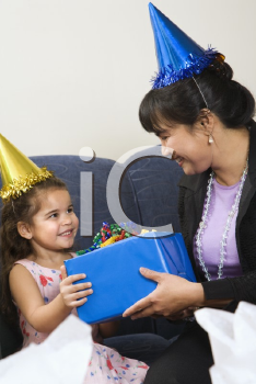 Royalty Free Photo of a Mother Giving Her Daughter a Present at a Birthday Party