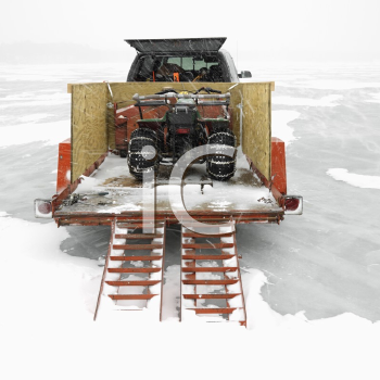 Royalty Free Photo of a Trailer With an ATV Parked on a Frozen Lake in Green Lake, Minnesota, USA