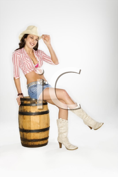 Young Caucasian woman dressed as cowgirl sitting on a barrel and tilting hat at viewer.