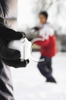 Royalty Free Photo of a Boy Holding a Snowball Ready to Throw it at a Boy in the Background