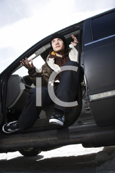 Royalty Free Photo of a Confident Male Teenager Sitting in a Car Making a Hand Gesture