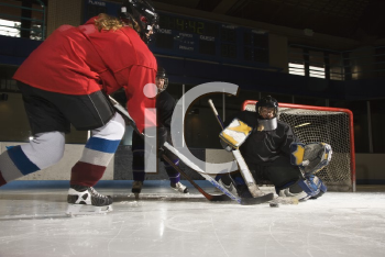 Royalty Free Photo of Hockey Players Trying to Make a Goal as a Goalie Protects the Net
