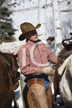 Royalty Free Photo of a Male Wrangler Putting a Saddle on a Horse