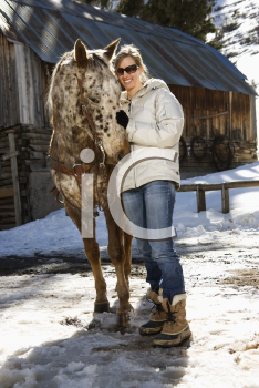 Royalty Free Photo of a Woman Petting a Horse