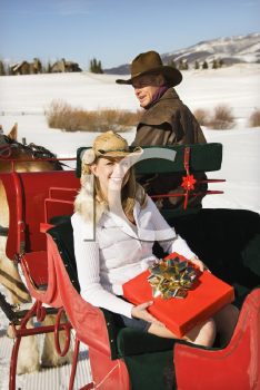 Royalty Free Photo of a Woman Holding a Present While a Man Drives a Horse-Drawn Sleigh