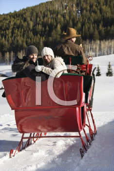 Royalty Free Photo of a Man Driving a Horse Drawn Sleigh With a Young Couple Looking Back