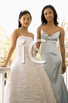 Royalty Free Photo of a Bride and the Maid of Honor Leaning Against a Railing