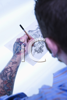 Royalty Free Photo of a Male Tattoo Artist Drawing a Tattoo on a Light Table