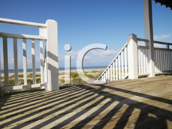 Royalty Free Photo of a View of Beach From Porch With Railing Casting Shadow on Wooden Deck at Bald Head Island, North Carolina