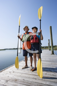 Royalty Free Photo of a Couple Standing on a Boat Dock Holding Paddles and Smiling