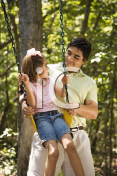 Royalty Free Photo of a Father Pushing His Daughter on a Swing and Smiling