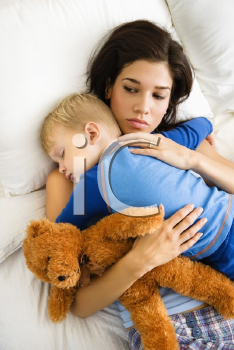 Royalty Free Photo of a Mother With Toddler Son Sleeping in Bed