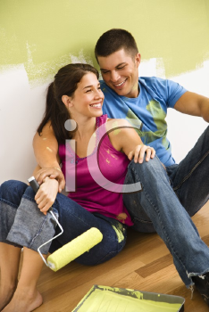 Royalty Free Photo of a Couple Sitting on the Floor Smiling Taking a Break From Painting