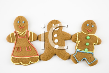 Three male and female gingerbread cookies holding hands.