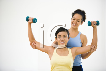 Royalty Free Photo of a Woman Lifting Weights While Another Woman Helps Position Her Arms