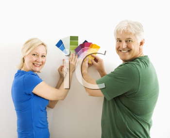 Royalty Free Photo of a Middle-Aged Couple Comparing Paint Swatches