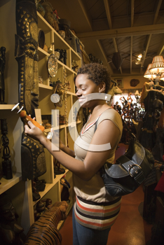 Smiling African American woman standing and looking at a candlestick or vase in a retail display. Vertical format.
