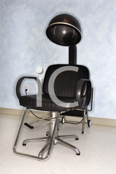 Empty styling chair and hair dryer at a salon.  Vertical shot.