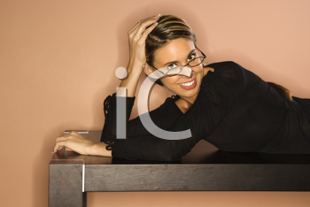 Attractive young woman lying on a table looking over her glasses. Horizontal shot