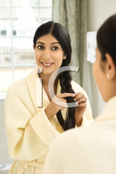 Reflected view of a young woman looking in the mirror at her long black hair. Vertical shot.