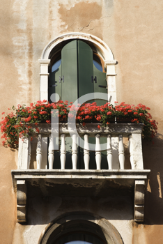 Low angle view of arched window with balcony and flowers in Venice, Italy. Vertical shot.