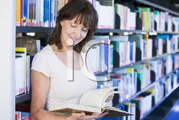 Royalty Free Photo of a Young Woman Reading in a Library