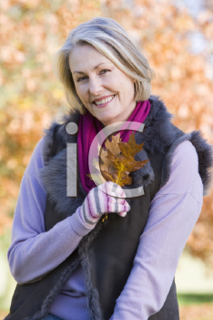 Royalty Free Photo of a Woman Outside Holding Leaves