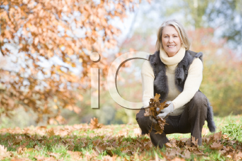 Royalty Free Photo of a Woman Playing in the Leaves