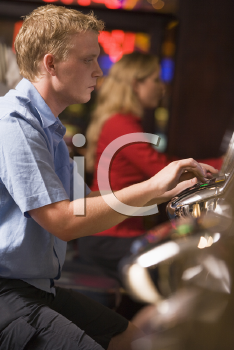 Royalty Free Photo of a Man Playing a Slot Machine