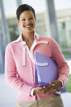 Royalty Free Photo of a Smiling Teacher With Notebooks