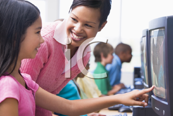 Royalty Free Photo of a Teacher Talking to a Student at a Computer
