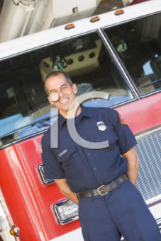 Royalty Free Photo of a Firefighter in Front of a Firetruck