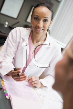 Royalty Free Photo of a Female Doctor Talking to a Woman
