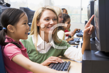 Royalty Free Photo of a Teacher Helping a Student at a Computer