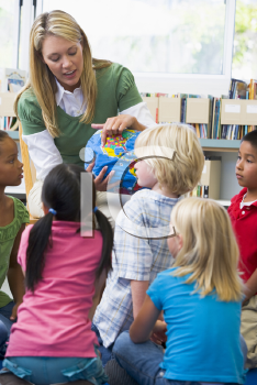 Royalty Free Photo of a Teacher Showing Her Students a Globe